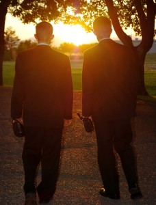 Mormon missionaries walking toward sunset