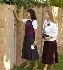 sister missionaries knocking at a gate