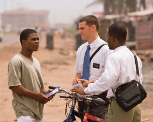 Missionaries talking to man on dirt road