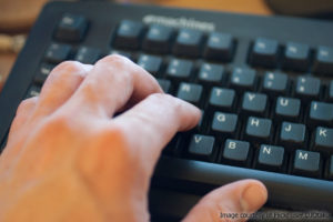 hand and computer keyboard